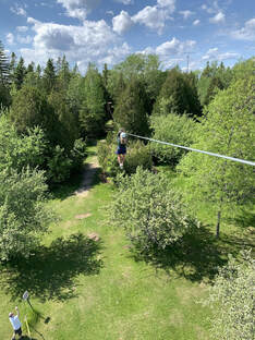 Woman zip lining into the trees